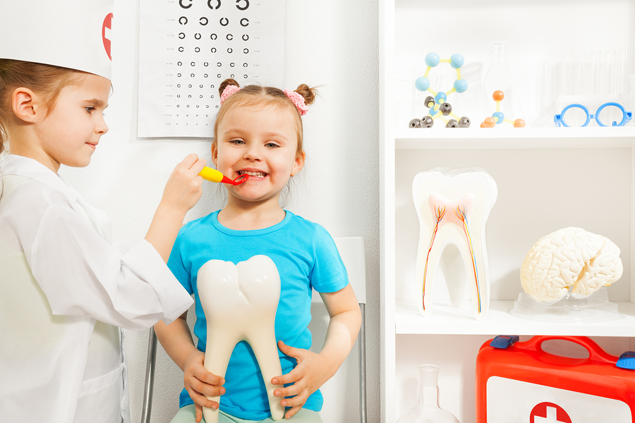 Young girls playing visit the dentist