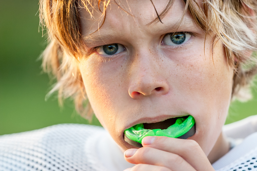 young athlete with a green mouth guard