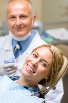 A dentist standing behind a woman smiling in a dental chair
