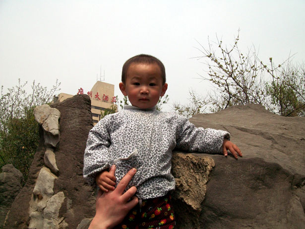 toddler outside posing by a large rock