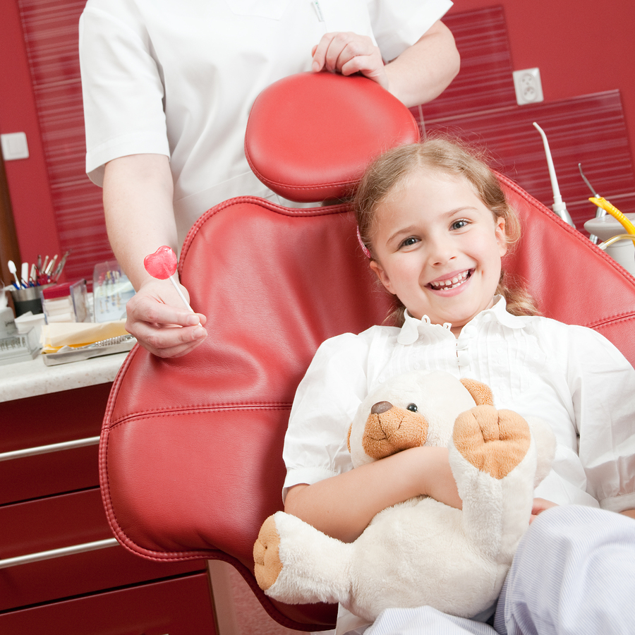 a girl pediatric patient in a dental chair holding a stuffed bear, with a dental professional standing behind the chair holding a lollipop