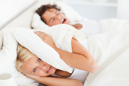 wife cover her ears with her pillow while her husband snores